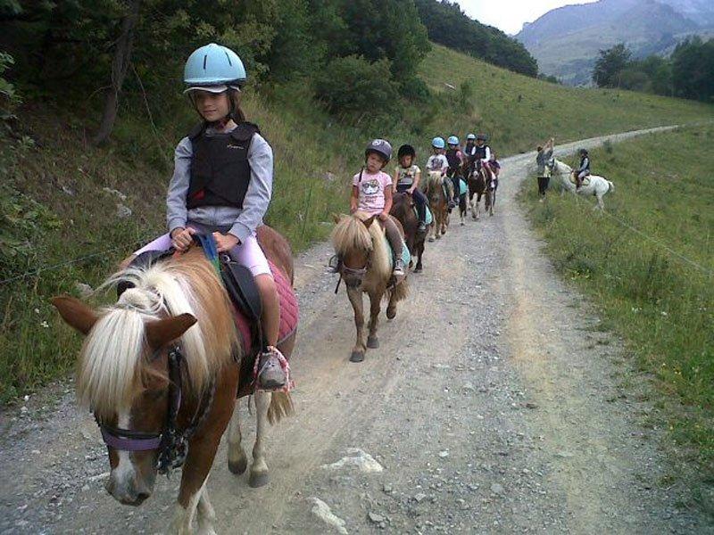 Gruppe von Kindern am Ponyreiten