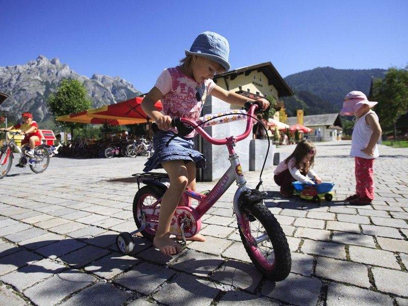 Kinder auf Fahrrädern am Dorfplatz